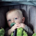 baby in a car seat with a binky in his mouth