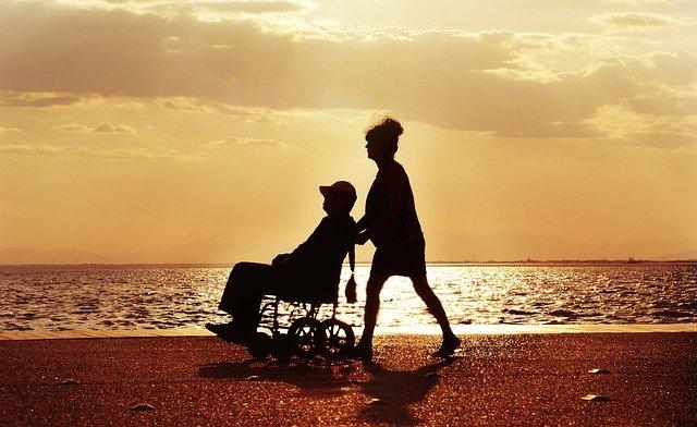 woman pushing man on wheelchair