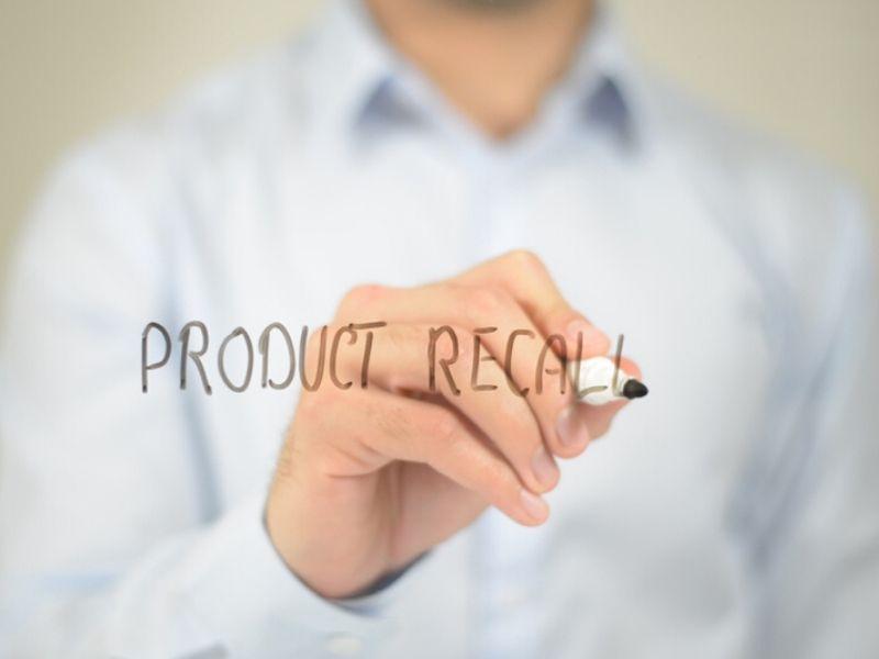 man writing product recall on glass